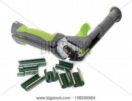 fence stapler in front of white background