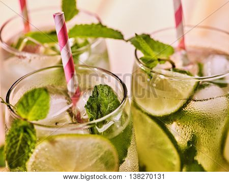 On wooden boards top of three glasses with alcohol cocktail drink and ice cubes. Drink number hundred forty three cocktail mohito and cube ice with striped straw. Country life. Light background.