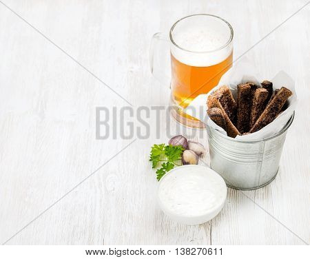 Beer snack set. Pint of pilsener in glass mug and rye bread croutons with garlic cream cheese sauce over white painted old wooden background, top view, copy space, selective focus