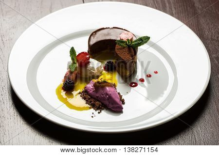 Chocolate souffle cake and ice cream fruit sherbet decorated with berries sweet sauce flower mint on wooden background