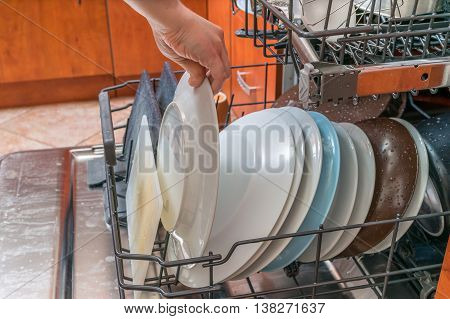 Female Hand Is Putting Dirty Plate In Dishwasher.