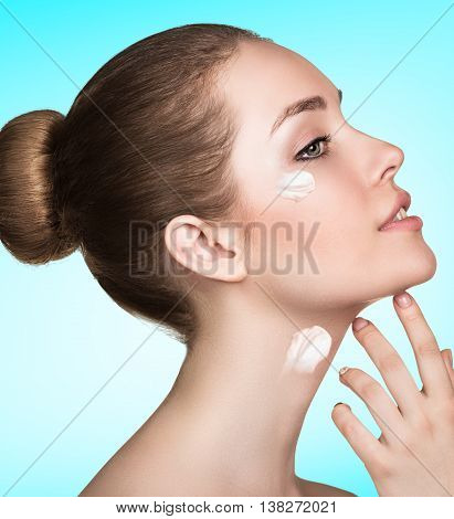 Beautiful model applying cosmetic cream on her face over blue background