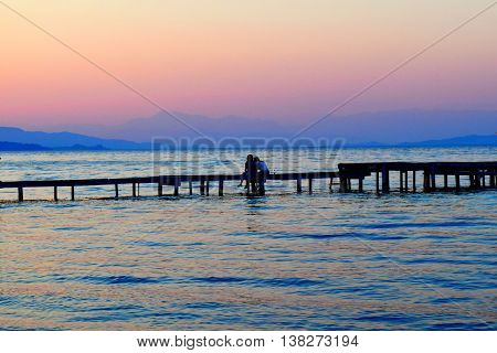 Couple in love, watching the sunset on the Pier in Corfu.