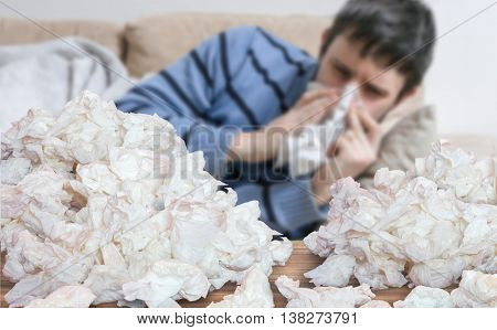 Funny Sick Man Who Has Flu Or Cold Is Blowing His Nose. Pile Of