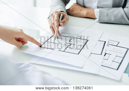 Close-up image of realtor showing blueprint of house to clients