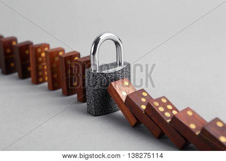 Lock blocked dominoes row on grey background