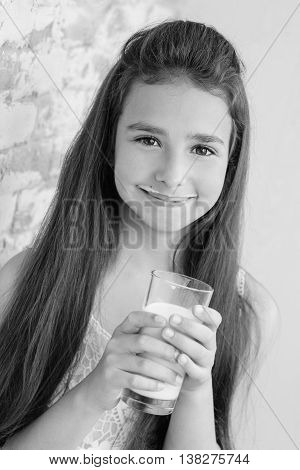 Cute little girl drinking milk on a white background ( black and white )