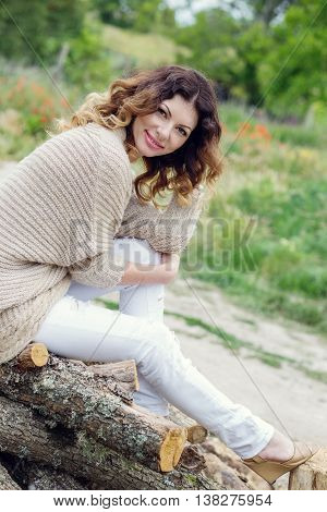 Happy beautiful young woman sitting on logs in the spring time
