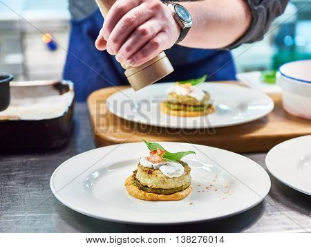 Cook Sprinkles Seasoning In Dish With Fish Cutlet In Restaurant