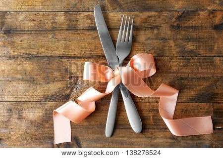Fork and knife with color ribbon on wooden table