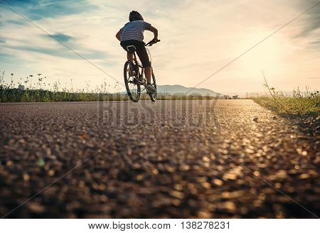 Boy rides a bicycle in the sunset light