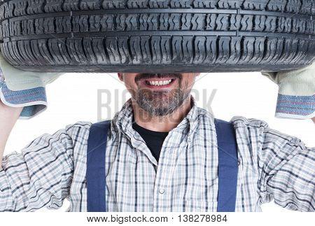 Closeup Of Happy Mechanic Holding Wheel On Head