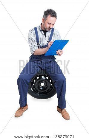Mechanic Sitting On Wheel And Writing On Checklist