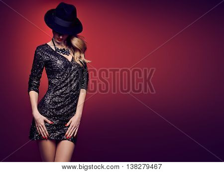 Fashion woman in Glamour Sequin black dress. Stylish Luxury Party lady. Blond sexy Model girl, Fashion hat, Trendy luxury Hairstyle. Fashion Makeup, shiny fashion Accessories. Unusual creative Outfit