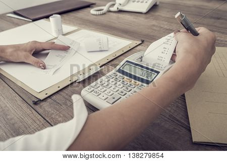 Retro image of accountant or businesswoman balancing the books checking the figures on a ledger with an adding machine close up view of her hands and paperwork.