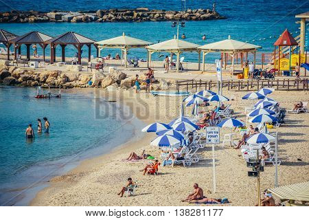 Tel Aviv Israel - October 18 2015. People sunbathes on the beach next to Hilton Hotel in Tel Aviv