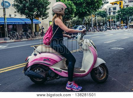 Tel Aviv Israel - October 19 2015. Woman rides on a SYM Mio 100 motor scooter on the street in Tel Aviv
