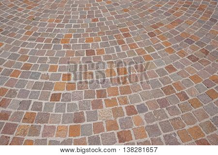 background of curved pavement with red granite blocks