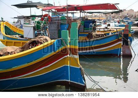 Old Maltese traditional Luzzu boats tied up at the quay