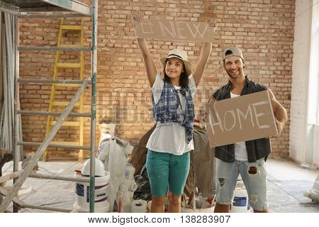 Young couple holding new home text at renovation site.