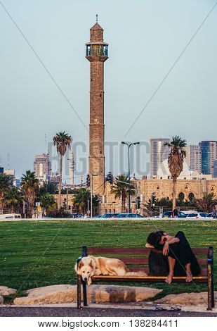 Tel Aviv Israel - October 21 2015. Woman with her dog rests on a bench in small park in Tel Aviv. View with Hassan Bek Mosque on background