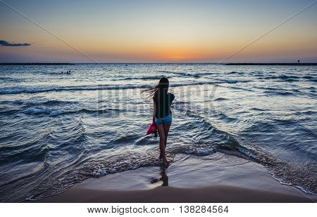 Tel Aviv Israel - October 21 2015. Girl stands on a seashore against the backdrop of the setting sun in Tel Aviv