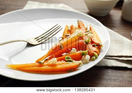 Plate of slices baby carrots with herbs on wooden table closeup