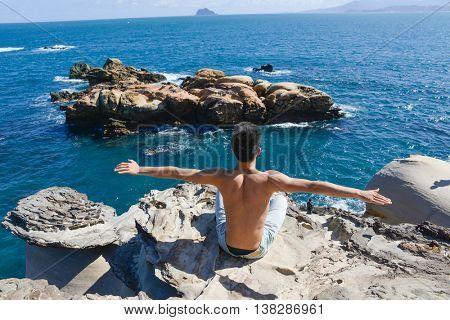 Healthy man doing yoga sitting back on rocks at beach
