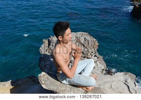 Young man doing yoga sitting on rocks at beach