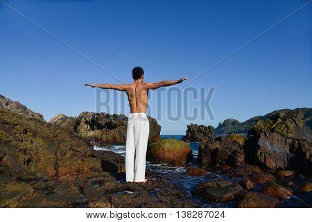 Healthy man doing yoga back on rocks at beach
