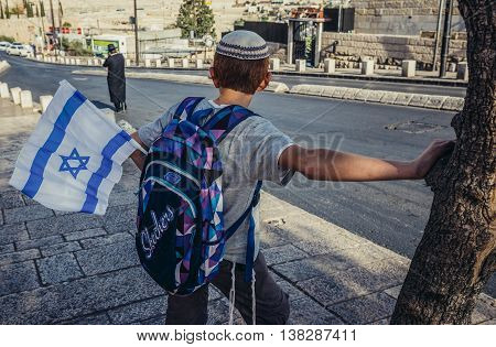 Jerusalem Israel - October 22 2015. Israeli boy with national flag waits for the bus in Jerusalem