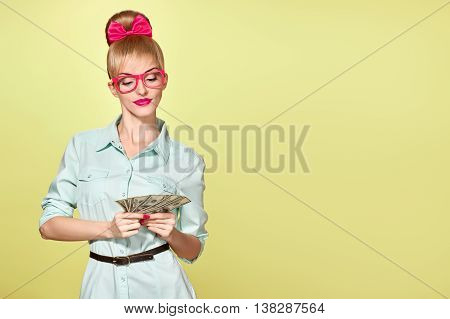 Fashion. Woman with Dollar Bill, cash in Stylish Glasses Having Fun. Playful Blonde girl with Glamour Pinup hairstyle, Trendy fashion Outfit, red bow Makeup, Blue Eyes. Money dollar, banking finance
