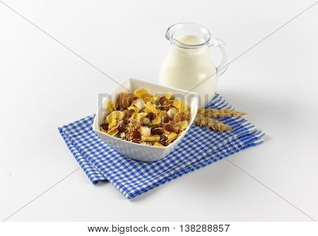 bowl of corn flakes and cereals with jug of milk on checkered dishtowel