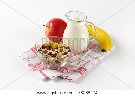 bowl of oat flakes, jug of milk and fruit on checkered dishtowel