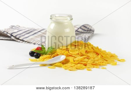 pile of corn flakes and glass of white yogurt on white background