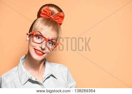 Fashion. Nerd Woman in Stylish Glasses Having Fun. Hipster fashion girl think, idea. Playful nerd Blonde with Glamour Pinup Stylish hairstyle, Trendy fashion, red bow Makeup. Unusual Creative, on pink