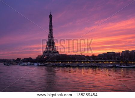 Fiery sunrise on the Eiffel Tower and Seine River in winter. Port de Suffren, Grenelle, 15th and 7th Arrondissements of Paris, France