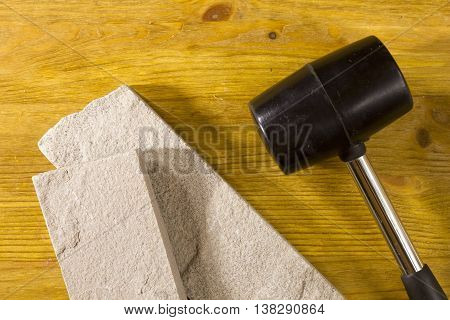 Black rubber mallet and facing stones on a wooden background