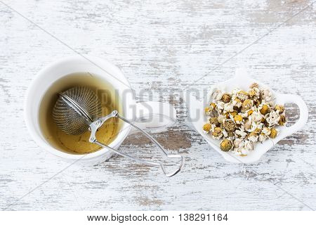 dried chamomile tea on a white wooden background