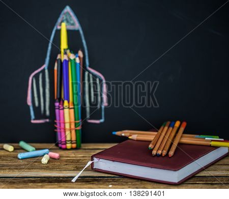Back school black background the missile made with pencils drawing crayons books school