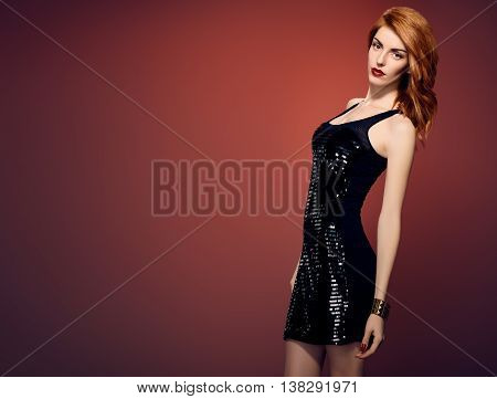 Fashion Redhead woman in Glamour Sequin black dress. Stylish Luxury party Outfit. Playful redhead sexy Model girl, Trendy fashion Hairstyle on red. Fashion Makeup, shiny Accessories. Unusual creative