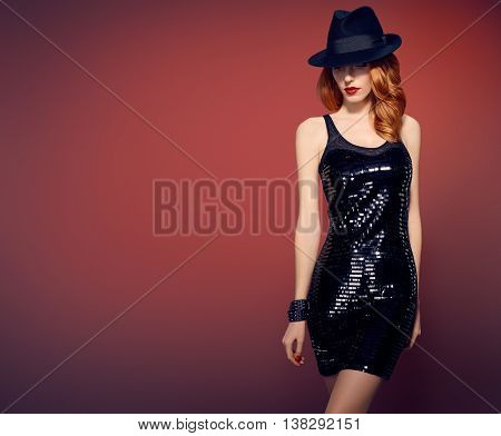 Fashion woman in Glamour Sequin black dress. Stylish Luxury party Outfit. Redhead sexy Model girl, Fashion hat, Trendy wavy Hairstyle on red. Fashion Makeup, shiny fashion Accessories.Unusual creative