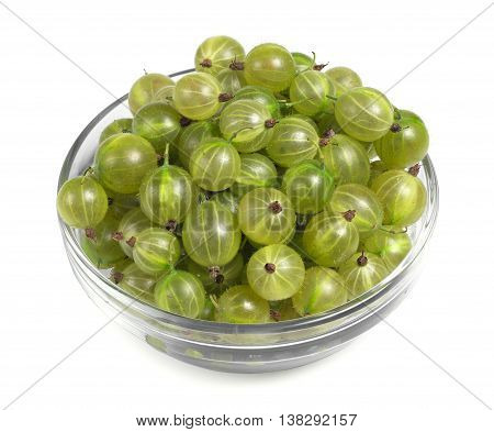 Green gooseberries in a glass bowl on white background