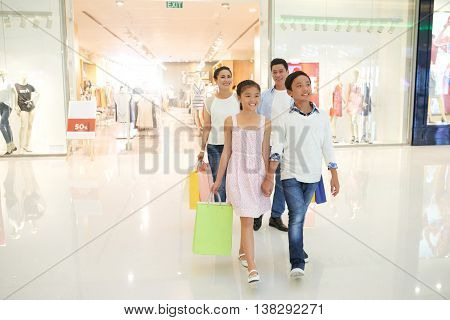 Vietnamese children and their parents walking in shopping mall together
