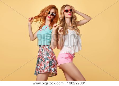 Fashion. Hipster woman in Stylish fashion Summer Outfit Having fun. Hipster sisters friends crazy cheeky emotions.Girl in Fashion sunglasses, Glamour hairstyle posing on yellow.Unusual Creative fashion