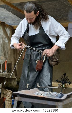 VILNIUS, LITHUANIA - MAY 24 : A blacksmith in medieval clothes, working in the street during a International Folklore Festival on May 24 2013 in Vilnius, Lithuania.