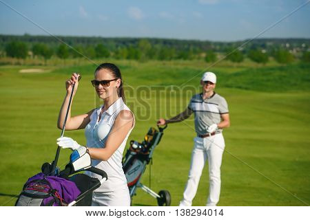Portrait of young sportive women golfer playing golf with man at sunny day