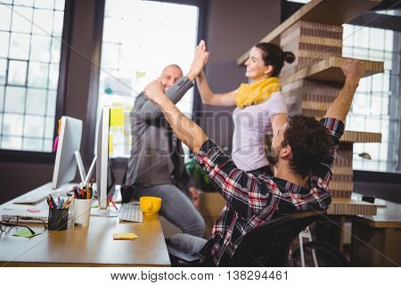 Business people cheering at computer desk in creative office
