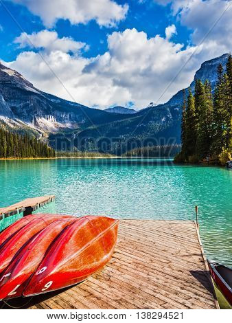 The concept of active tourism and vacation. Emerald Lake in the Canadian Rockies. Shiny red kayaks are dried upside down