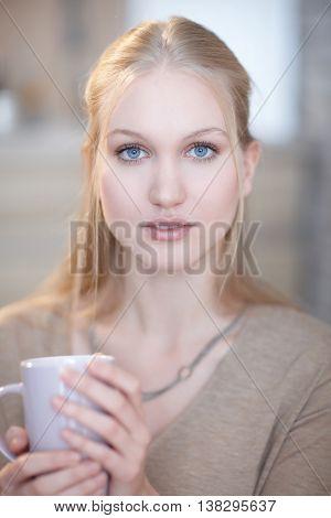 Portrait of innocent looking nordic woman holding tea mug, looking at camera, blue eyes.